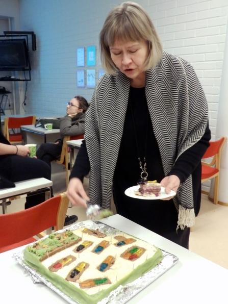 Kristiina leikkaa Kalmistopiirin kalmistokaivauskakkua arkeologian seminaarihuoneessa 2014.