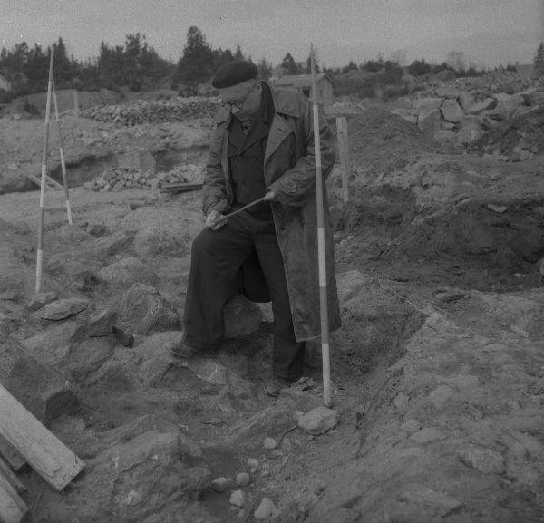 Jorma Leppäaho tutkiskelee keihäänkärkeä samaisella Urjalan Kunnalliskodin kaivauksella 1953. Leppäaho oli rautakauden tutkija, joka kaivoi 1950-luvulla mm. Mikkelin Visulahden ja Halikon Rikalan ristiretkiaikaisia/varhaiskeskiaikaisia kalmistoja. Hän oli kiinnostunut raudantyöstöstä ja aseistuksesta, ja hänen muistiinpanoihinsa perustuva aineisto julkaistiin postuumisti vuonna 1964. Teos sisältää kuvauksia yksittäisistä miekoista ja Leppäaholla onkin ollut suuri vaikutus myöhäisempään eurooppalaiseen miekkatutkimukseen. Kuva: Pekka Kosonen (?).