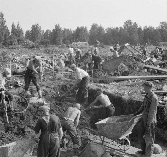 Imatran Voiman polttokenttäkalmiston kaivaukset käynnissä 1938. Kuvan ottanut Sakari Pälsi tuli tunnetuksi mm. erinomaisena valokuvaajana, ja häntä voi pitää kaivausten valokuvadokumentoinnin edelläkävijänä. Hämeenlinnaan Pälsi oli matkustanut, sillä Vanajan voimalaitoksen rakennustöihin liittyen hiilikentän kuorimistöissä oli paljastunut laaja viikinkiaikainen kalmisto. Kalmisto oli jo osittain tuhoutunut ja monet löydöistä kerättiin kentältä korituista maakasoista. Talletettua esineistöä on satoja, joukossa harvinaisuuksia, kuten leluksi arveltu rautainen mimiatyyrimiekka ja auran terä.