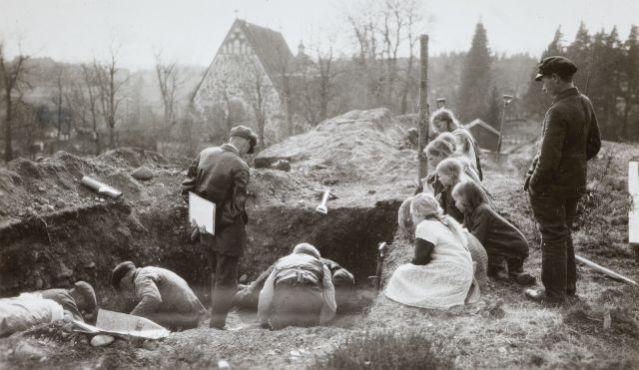 Humikkalan kalmistoa kaivetaan vuonna 1925. Kalmisto lötyi samana kesänä Maskun kirkon vieressä olevalta mäeltä soranotossa. Kaivauksessa löytyi 56 runsaasti varustettua ristiretkiaikaista hautaa. Naisten haudassa numero 32 säilyneiden kankaanjäänteiden pohjalta on rekonstruoitu ns. Maskun muinaispuku. Puku sisältää sinisen kaarihunnun, sinisen viitan, sinisen esiliinan, kellanruskean mekon ja vaalea hame. Humikkalan miekkahaudoista voi lukea lisää Kalmistopiiristä. Kuva: Sakari Pälsi.