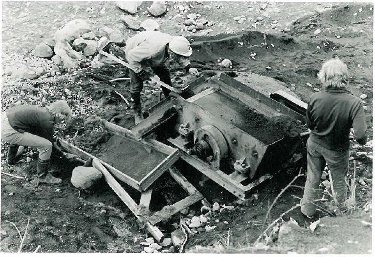 Vilusenharjun rikasta kalmistoa tutkittiin 1960-luvulla useana kesänä, ja vuonna 1971 alueelta poistettua maata käytiin läpi seulomalla irtolöytöjen talteen saamiseksi. Paikalla oli tuolloin useita käsiseuloja ja myös kuvassa näkyvä pieni koneseula, jota käytettiin seuraavasti: yksi lapioi maata seulaan, toinen poimi suurimmat esineet kourusta ja kolmas pienimmät kourun alla olevasta käsiseulasta.