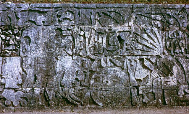 Kiveen kuvattu mestaus Chichen Itzassa. Vasemmalla oleva henkilö pitelee oikeanpuoleisen henkilön päätä samalla kun ihmisuhrin kaulasta virtaa veri käärmeiden muodossa. (Creative Commons)