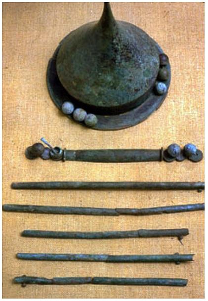 Piikkiön pronssinen, piikkilakkinen kilvenkupura ja sen yhteydessä löydetty kädensijan pronssihela (kuvassa kupuran alapuolella). Vanhempi roomalaisaika. © HY/Kulttuurien tutkimuksen laitos, Arkeologian oppiaine.