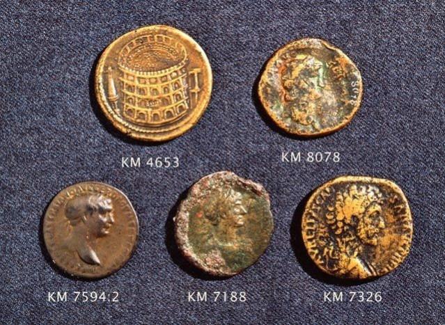 Joitakin Suomesta löytyneitä roomalaisia rahoja. Todennäköisesti tänne jo roomalaisaikana päätyneitä kolikoita ovat Hadrianuksen (keskellä alhaalla), Neron (oikealla ylhäällä) ja Trajanuksen (vasemmalla alhaalla) lyöttämät rahat. Ylhäällä vasemmalla oleva kolikko on väärennös ja alhaalla oikealla oleva on paljon myöhäisempää tuontia.